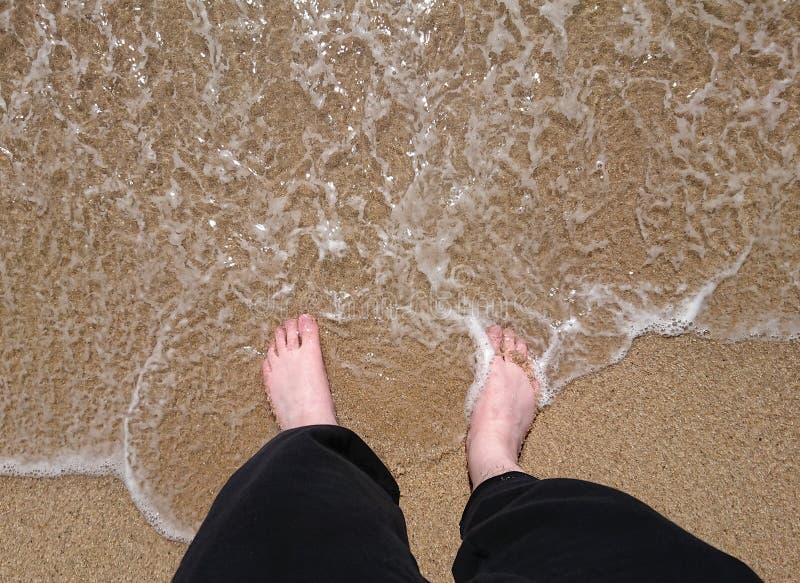 Mężczyzn cieki stoi na brzeg jak fala podołek na plaży w lecie Wierzcho?ka puszka strza? zdjęcie stock