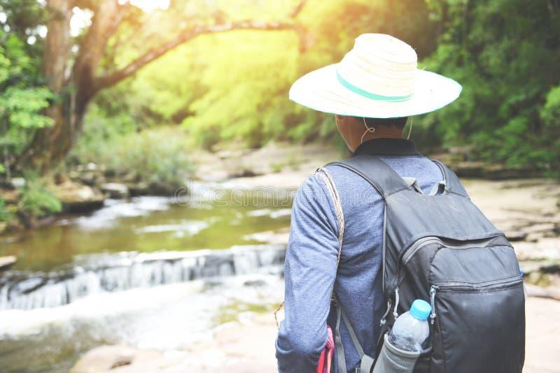 Mężczyzn wycieczkowiczy natury halny odprowadzenie z plecakami i siklawą w lasowej przygody podróży turystyce bawi się aktywność zdjęcia stock