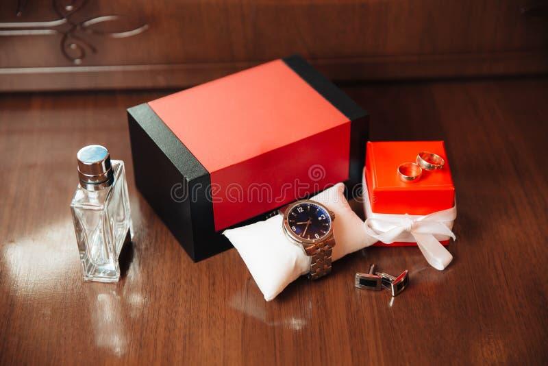 Mężczyzn zegarki, pachnidło, wristwatches, złoci pierścionki i cufflinks na tle brązu stół, target30_1_ obrazy stock