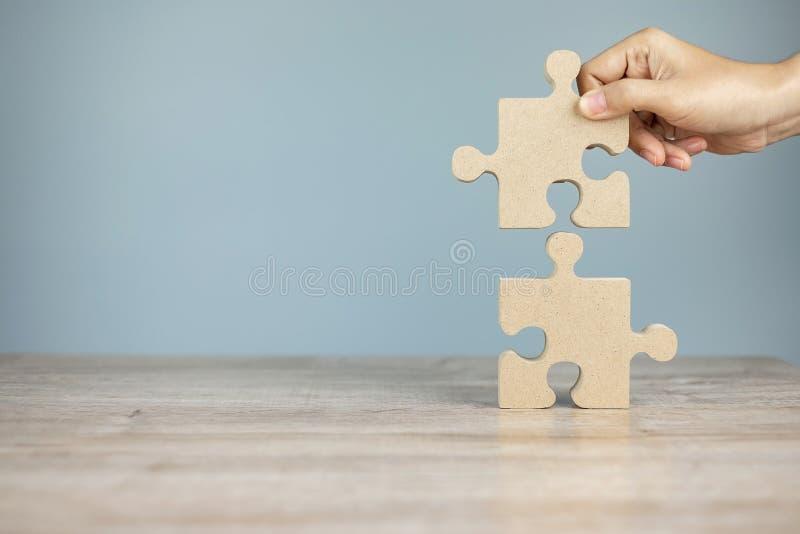 Mężczyzna łączący parę układanki, drewniana układanka na tle stołu Rozwiązania biznesowe, misja, sukces, cele i strategia obraz stock
