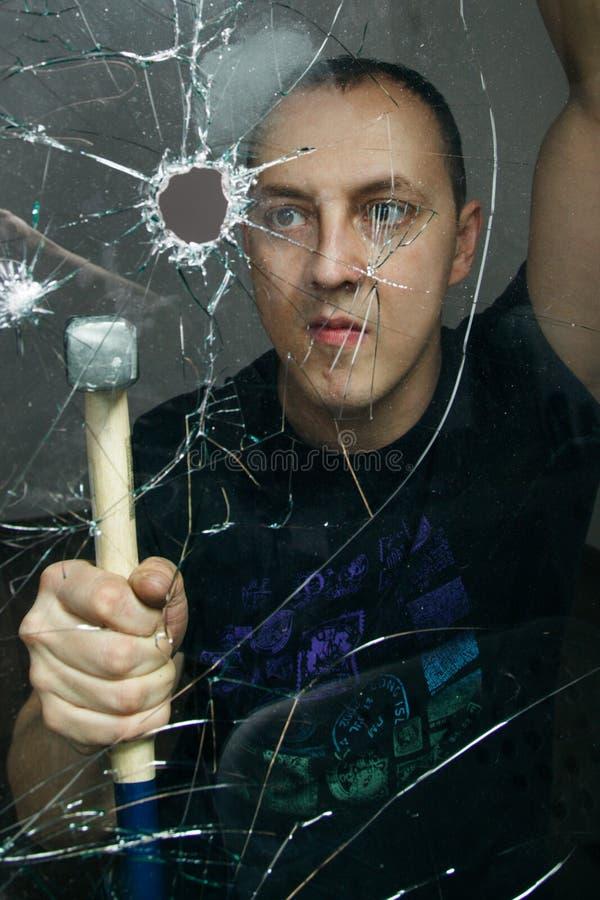 Mężczyzna łama szkło z młotem zdjęcie royalty free