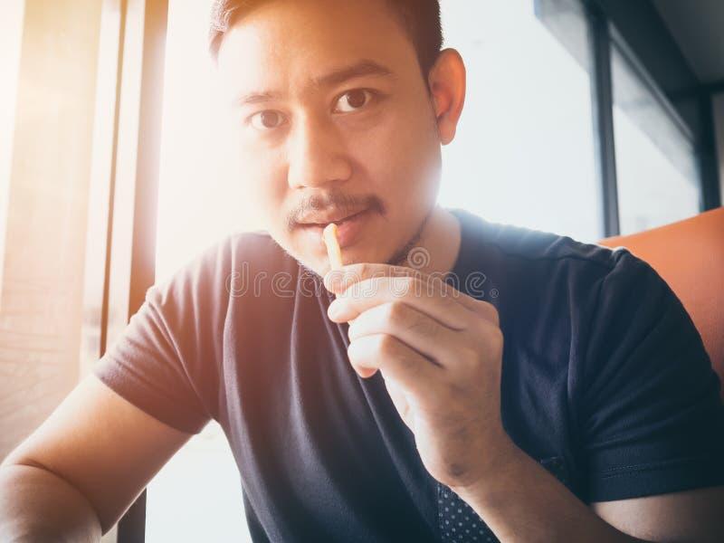 Mężczyzna łasowania francuza dłoniaki w kawiarni obraz royalty free