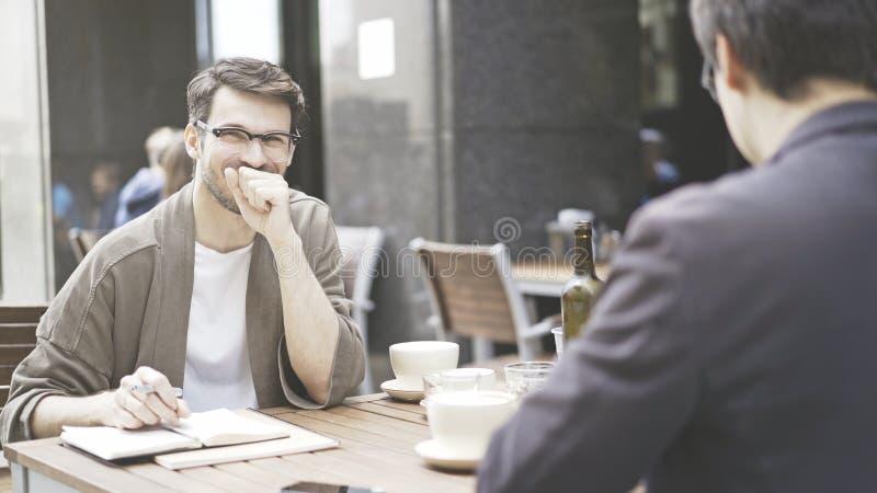 Mężczyzna śmia się przy kawiarnią outdoors w eyeglasses zdjęcia royalty free