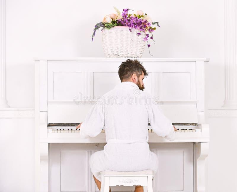 Mężczyzna śpiący w bathrobe siedzi przed fortepianowym instrumentem muzycznym w białym wnętrzu na tle, tylni widok utalentowany zdjęcie royalty free