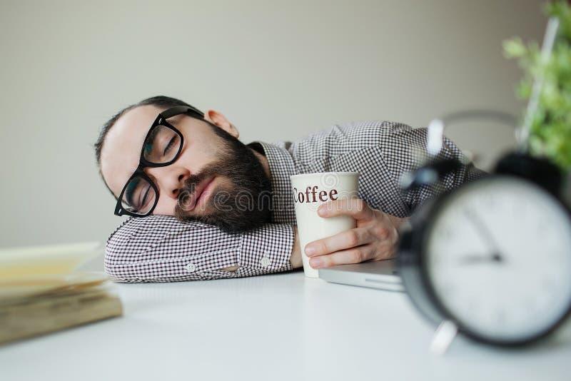 Mężczyzna śpi w biurze na stole nad laptopem z kawą w ręce fotografia royalty free