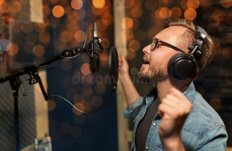 Mężczyzna śpiewa przy studiiem nagrań z hełmofonami zdjęcie stock