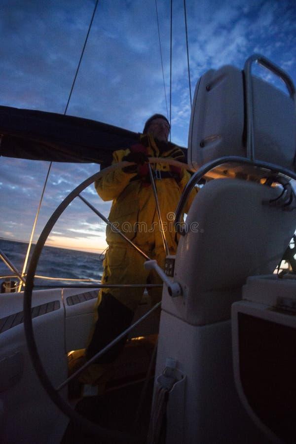 Mężczyzna żagla Sterownicza łódź W morzu Podczas zmierzchu fotografia stock