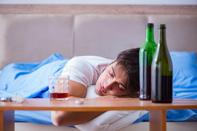Mężczyzna alkoholiczka pije w łóżku iść łama up depresję zdjęcia stock