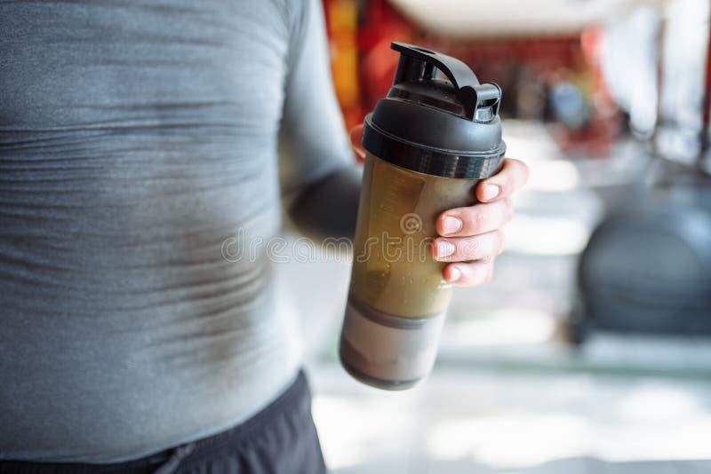 Mężczyzna atleta wziąć przerwę w szkoleniu i wodzie pitnej, z sport butelką w gym obraz stock