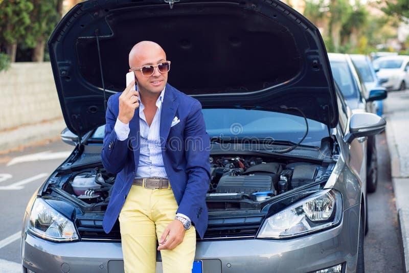 M??czyzna b?d?cy usytuowanym na jego samochodzie z otwartego kapiszonu szcz??liwy opowiada? telefonem zdjęcie stock