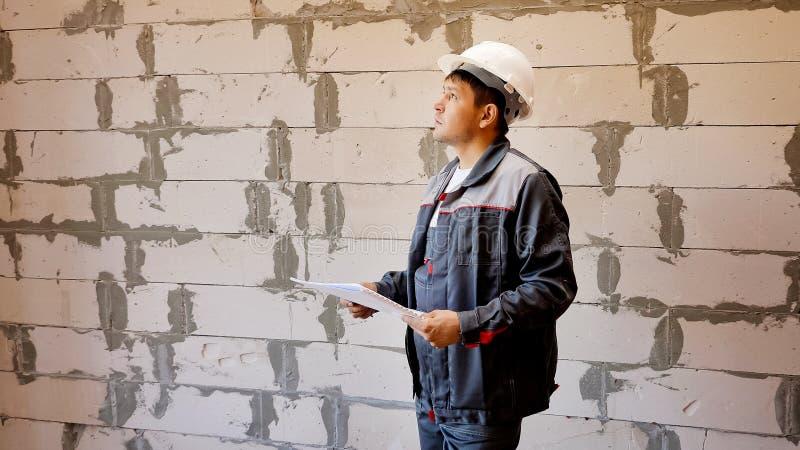 Mężczyzna bada pokój w budować w budowie z papierami obrazy royalty free