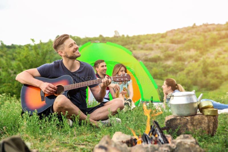 Mężczyzna bawić się gitarę blisko campingowego namiotu obraz royalty free
