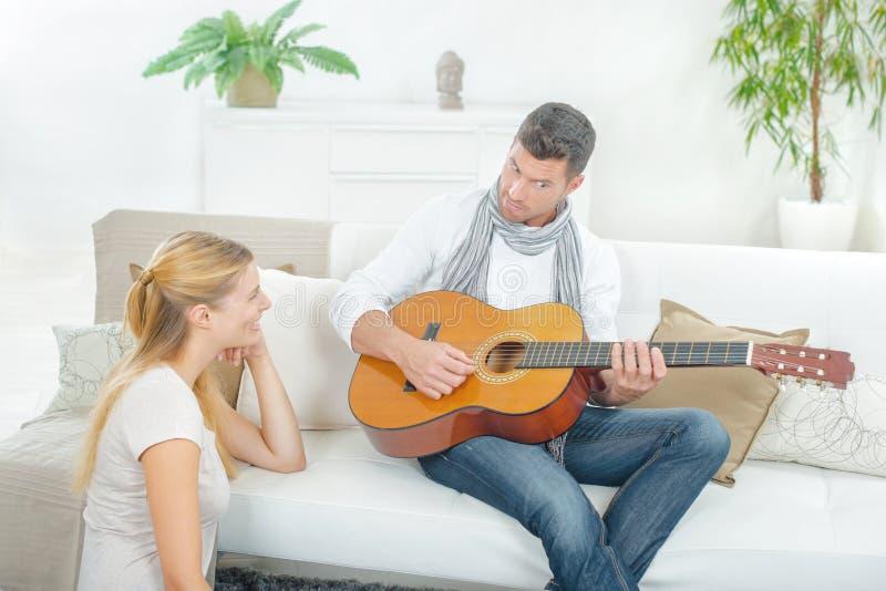 Mężczyzna bawić się gitarę dama fotografia stock
