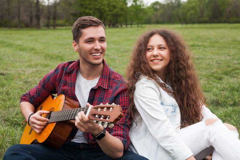 Mężczyzna bawić się gitarę dla dziewczyny zdjęcie stock