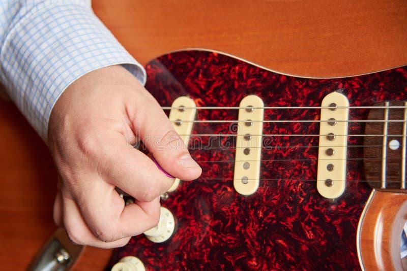 Mężczyzna bawić się gitarę elektryczną z mediatorem obraz stock