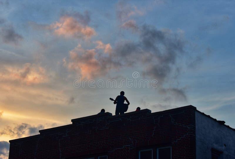 Mężczyzna Bawić się gitarę Na dachu budynek W zmierzchu obrazy royalty free