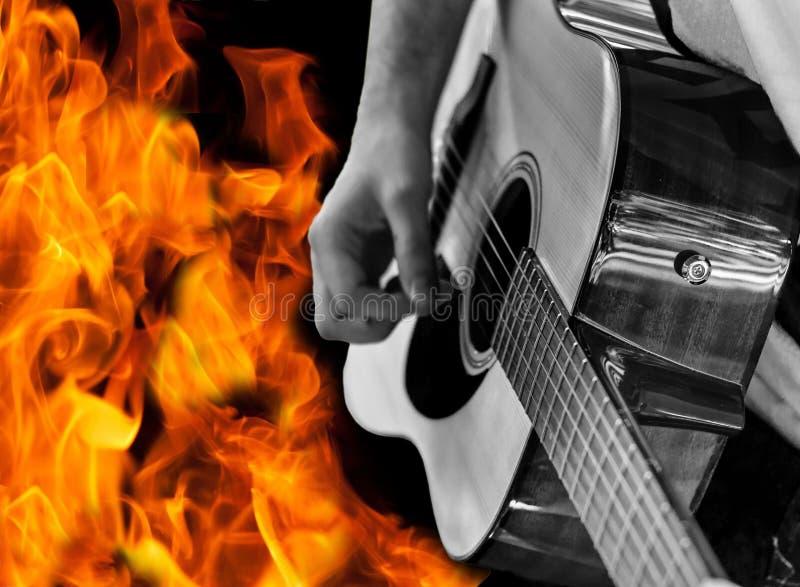 Mężczyzna bawić się gitarę przeciw pożarniczemu tłu obrazy stock