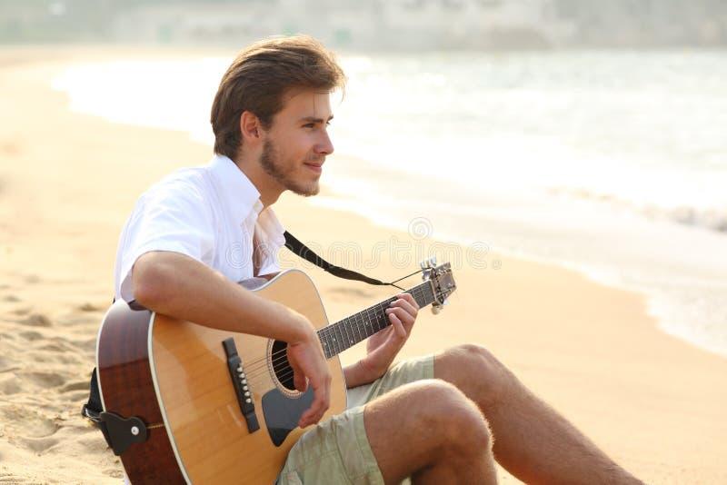 Mężczyzna bawić się gitary obsiadanie na plaży zdjęcie stock