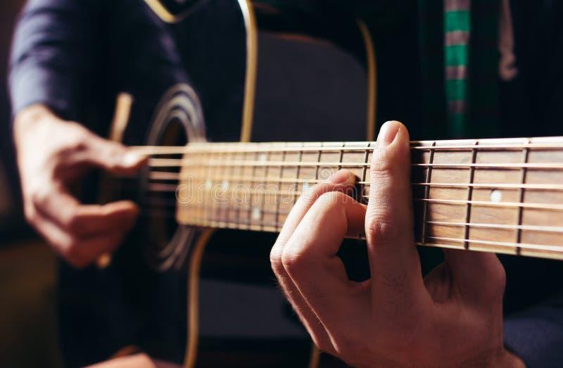 Mężczyzna bawić się muzykę przy czarną drewnianą gitarą akustyczną fotografia royalty free