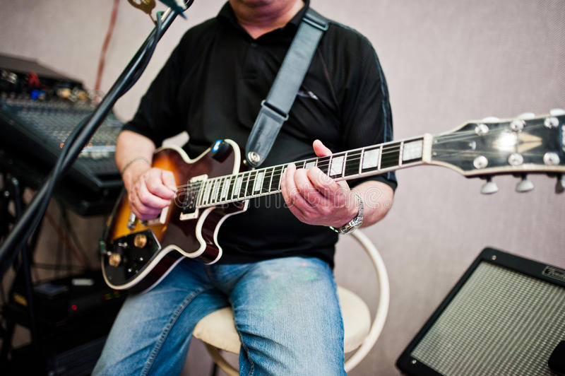 Mężczyzna bawić się na gitarze elektrycznej przy sceną obrazy royalty free