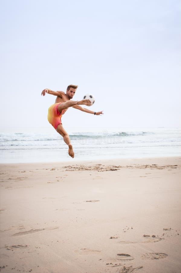 Mężczyzna bawić się na plaży z futbolem fotografia stock