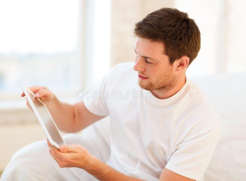 Mężczyzna bawić się z pastylka komputerem osobistym w domu zdjęcia royalty free