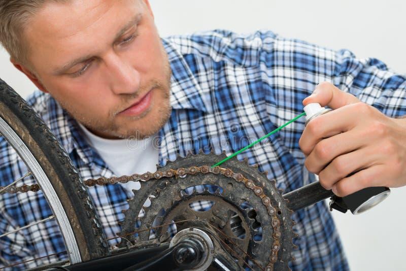 Mężczyzna bicyklu Oliwiący łańcuch obrazy royalty free