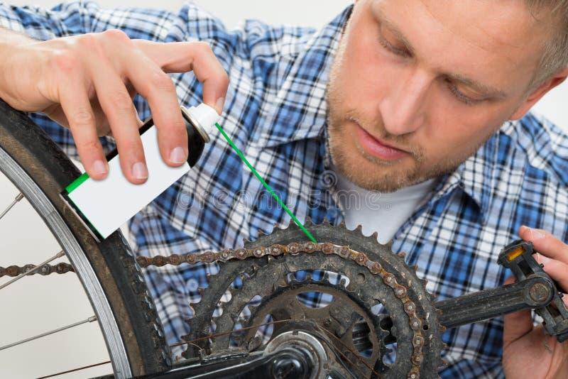 Mężczyzna bicyklu Oliwiący łańcuch obraz stock