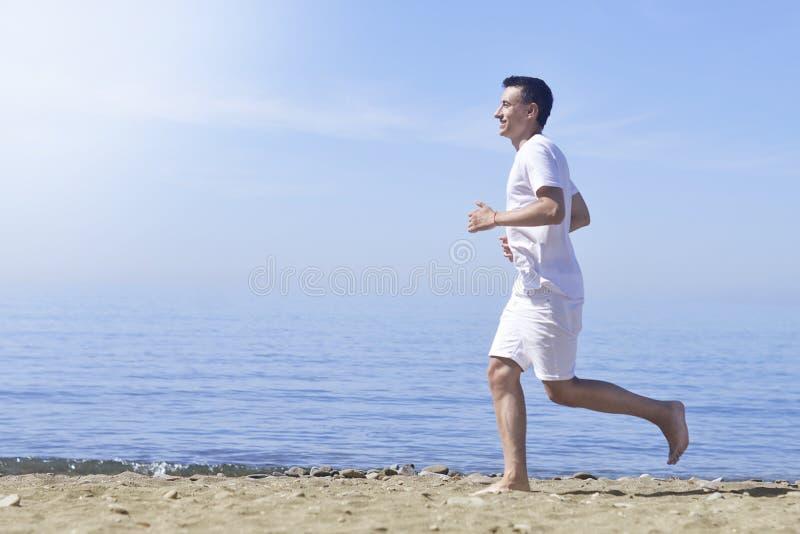 Mężczyzna bieg na pogodnej plaży Unrecognizable ciało jogging na ocean plaży Biegać na tropikalnej plaży Atrakcyjny mężczyzna cie obraz stock