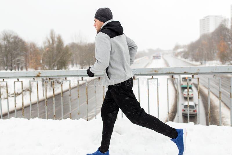 Mężczyzna bieg wzdłuż śniegu zakrywał zimy bridżową drogę fotografia stock
