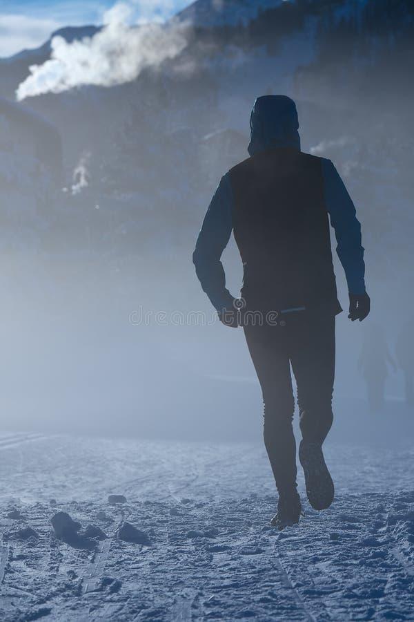 Mężczyzna biega na śniegu w zimnie zima obrazy stock