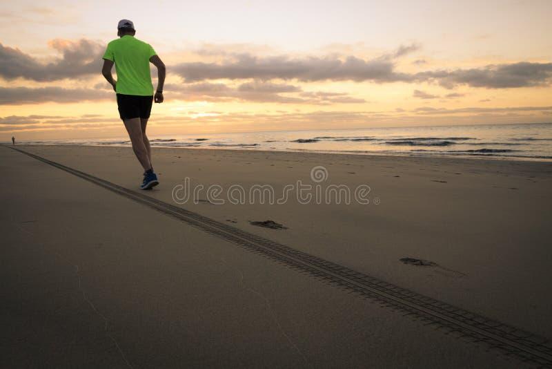 Mężczyzna biega plażą zdjęcia stock