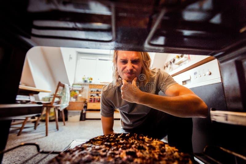 Mężczyzna Bierze Burnt pizzę Od kuchenki zdjęcie royalty free