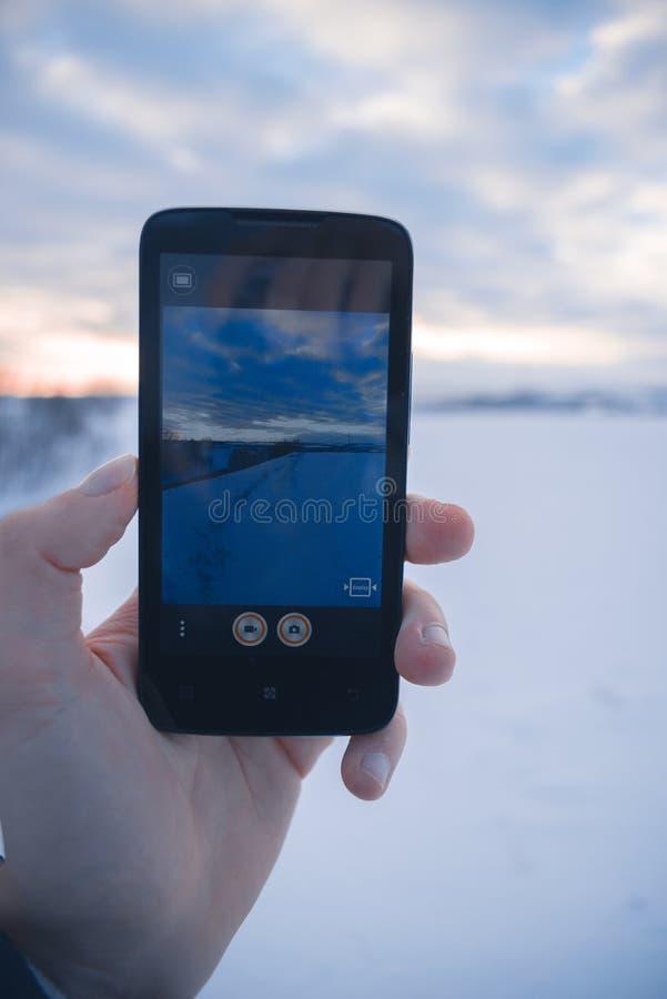 Mężczyzna bierze obrazki zima krajobraz na telefonie komórkowym obrazy royalty free