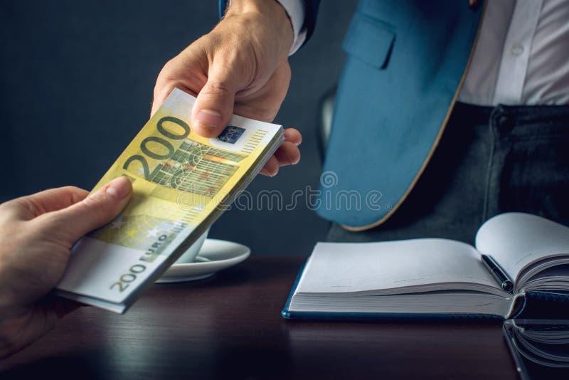 Mężczyzna biznesmen w kostiumu bierze pieniądze ręki Łapówka w postaci euro rachunków Pojęcie korupcja i łapówkarstwo obrazy royalty free