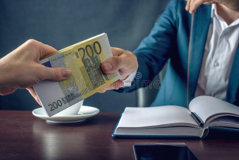 Mężczyzna biznesmen w kostiumu bierze pieniądze ręki Łapówka w postaci euro rachunków Pojęcie korupcja i łapówkarstwo obrazy stock