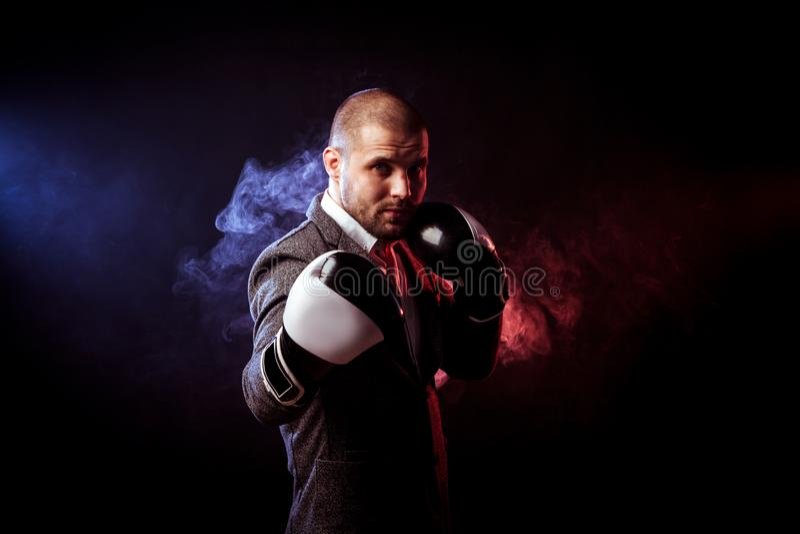 Mężczyzna biznesmen w szarość nadaje się i bokserskie rękawiczki fotografia royalty free