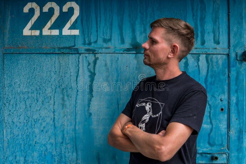 Mężczyzna blisko błękitnej kruszcowej ściany Młody europejski mężczyzna przy ulicą obraz stock
