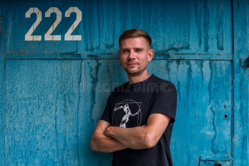 Mężczyzna blisko błękitnej kruszcowej ściany Młody europejski mężczyzna przy ulicą zdjęcie royalty free