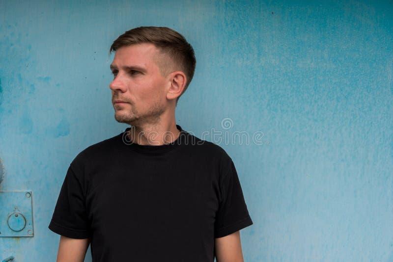Mężczyzna blisko błękitnej kruszcowej ściany Młody europejski mężczyzna przy ulicą obraz royalty free