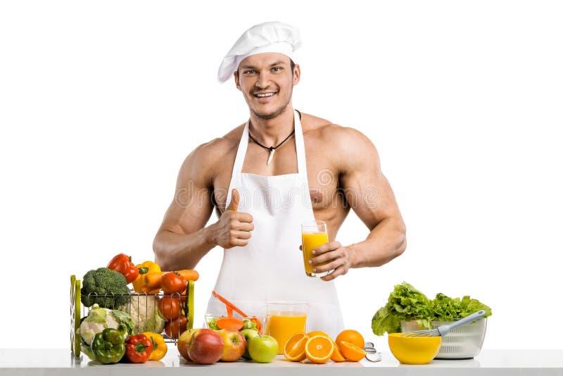 Mężczyzna bodybuilder kucharz, gotujący świeżo gniosącego vegetab i sok obraz stock