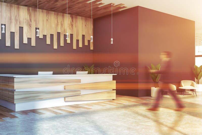 Mężczyzna chodzi blisko szarego recepcyjnego biurka obrazy royalty free