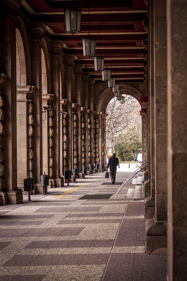 Mężczyzna chodzi między kolumnami wielki stary budynek tunel tworzący wielkimi kolumnami zdjęcia royalty free