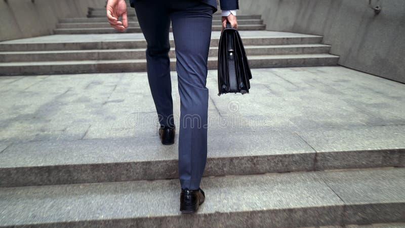 Mężczyzna chodzi w garniturze na piętrze trzymający teczka początek dzień roboczy obrazy royalty free