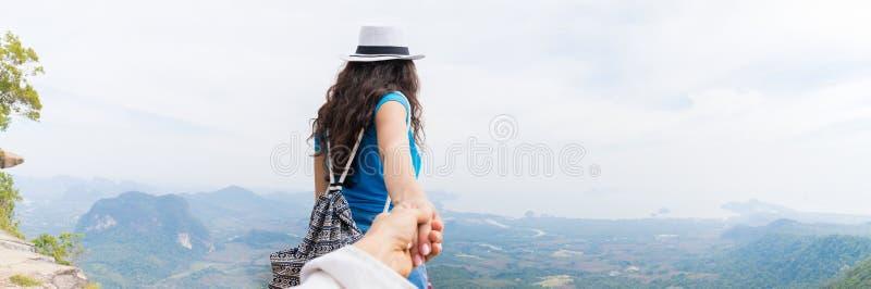 Mężczyzna chwyta kobiety ręka, Turystyczna para Z plecakiem Na góra wierzchołka panoramy Z powrotem Tylni widoku Cieszy się Piękn fotografia royalty free