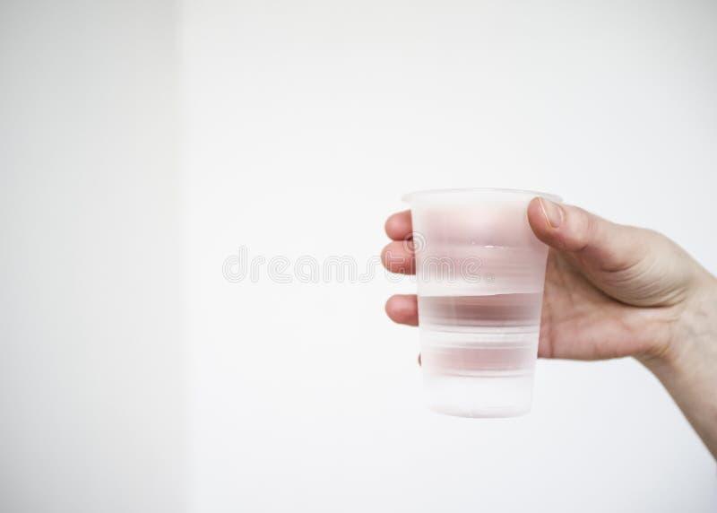 Mężczyzna chwyty w jego wręczają plastikowy matt szkło czysty pije w fotografia stock