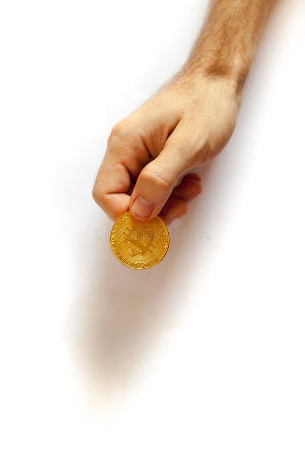 Mężczyzna chwyty w jego wręczają złocistej monety bitcoin zdjęcia stock