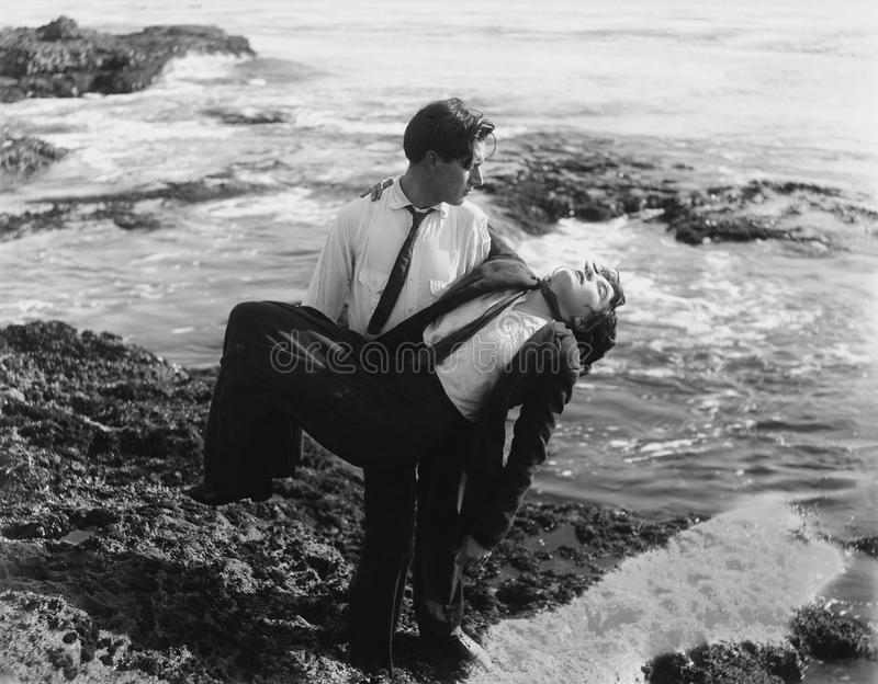 Mężczyzna ciągnie nieżywego mężczyzna z oceanu (Wszystkie persons przedstawiający no są długiego utrzymania i żadny nieruchomość  obrazy royalty free