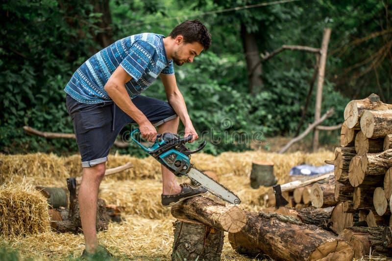 Mężczyzna ciapania drewno z piłą łańcuchową obraz stock