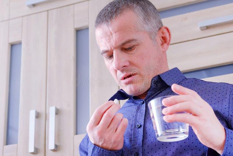 Mężczyzna cierpi od migren Iść brać migreny pigułkę Trzyma szkło woda migreny zdjęcie royalty free